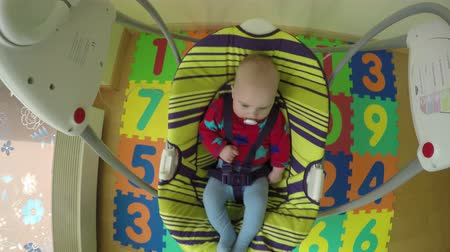 мягкий : 5 month baby girl swing in electric bounce swing at home. 4K UHD wide angle shot. Camera hang on swing handle. Стоковые видеозаписи