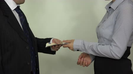 oblek : Business people pay euro cash money banknotes and handshake on white background. Man in suit and woman in shirt make a deal. Bribery in government. Closeup shot. 4K UHD video clip.