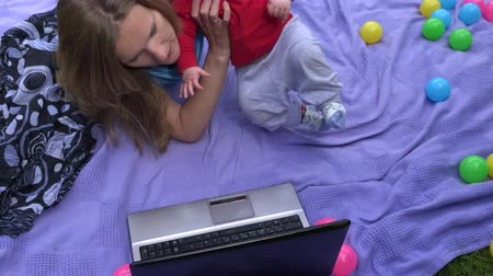 sulky : Calm business woman try to work on laptop computer with her newborn baby on plaid in garden. Static shot. 4K