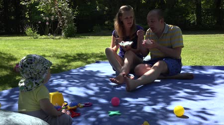 spent : Happy loving husband and wife eat ice cream on plaid and cute infant baby child look at them. Happy family spent time in garden. Static shot. 4K Stock Footage