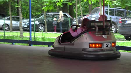spent : VILNIUS, LITHUANIA - MAY 31,2015: Happy mother with daughter drive bumper dodge car in amusement park on May 31, 2015 in Vilnius, Lithuania. Follow shot. 4K