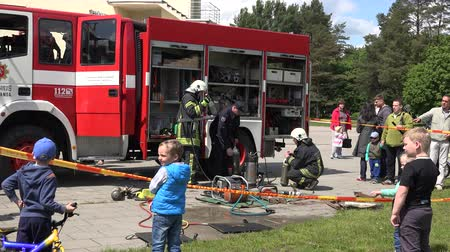 spent : VILNIUS, LITHUANIA - MAY 31, 2015: children kids with parents enjoy firefighter men performance near rescue truck in public park on May 31, 2015 in Vilnius, Lithuania. Zoom in shot. 4K