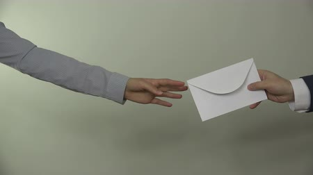 dát : People hands exchange envelope on white background. Male man in suit give envelope gift for business partner woman. Bribery in government. Closeup shot. 4K UHD video clip.