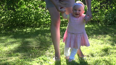 ilk : Cute funny happy baby girl in pink dress making her first steps on green lawn in sunny summer garden with mother holding her hands supporting by learning to walk. Static shot. 4K Stok Video