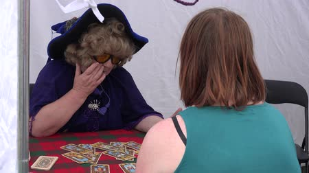astrologer : BELMONTAS, LITHUANIA - JUNE 20, 2015: elderly fortune teller predict the future with tarot card to young woman outdoor on June 20, 2015 in Belmontas, Lithuania. 4K UHD video clip.