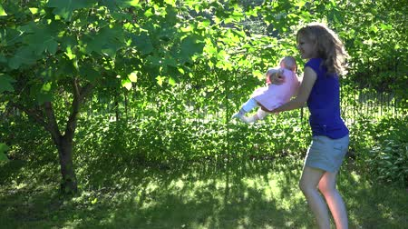 penetrating : active woman with baby daughter have fun near green tree branches in evening sunlight penetrating through leaves. Static shot. 4K