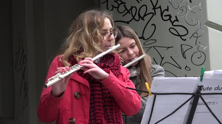 fife : VILNIUS, LITHUANIA - MAY 16, 2015: Young musician women girls play with flute in old town street free event on May 16, 2015 in Vilnius, Lithuania. Street music day. Zoom out shot. 4K