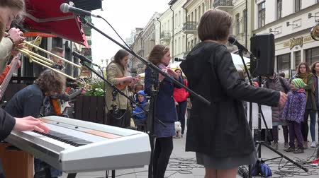 waggle : VILNIUS, LITHUANIA - MAY 16, 2015: musicians group with vocalist woman sing and play popular music outdoors on May 16, 2015 in Vilnius, Lithuania. Street music day. Static shot. 4K