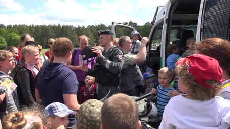 bulletproof : VILNIUS, LITHUANIA - MAY 31,2015: Policeman cop show police equipment shield helmet truncheon for children kids on May 31, 2015 in Vilnius, Lithuania. National children day. Static shot. 4K