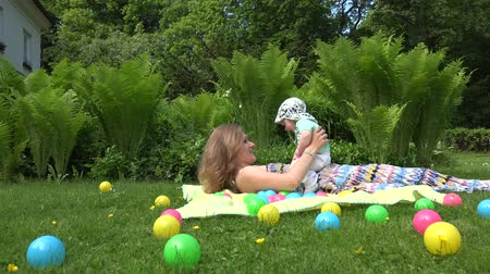 spent : Happy mother with baby son lay on plaid in meadow between colorful balls. Right side sliding shot. 4K