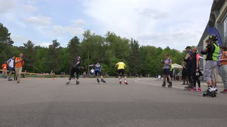 participante : VILNIUS, LITHUANIA - MAY 23, 2015: Young roller skater men start participate in speedskating competition on May 23, 2015 in Vilnius, Lithuania. Active sport. Panorama follow shot. 4K