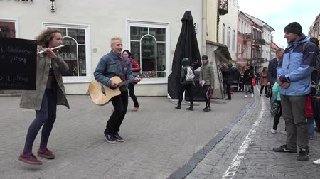 fife : VILNIUS, LITHUANIA - MAY 16, 2015: Young cute musicians pair boy and girl play guitar, flute and sing outdoors on May 16, 2015 in Vilnius, Lithuania. People tourists bypass. Street music day. 4K