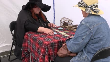 astrologer : BELMONTAS, LITHUANIA - JUNE 20, 2015: witch turn tarot cards on the table to women outdoor on June 20, 2015 in Belmontas, Lithuania. 4K UHD video clip. Zoom out view.