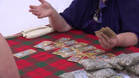 astrologer : BELMONTAS, LITHUANIA - JUNE 20, 2015: funny tarot cards reader witch with glasses predict future life for client woman on June 20, 2015 in Belmontas, Lithuania. Zoom out shot. 4K Stock Footage