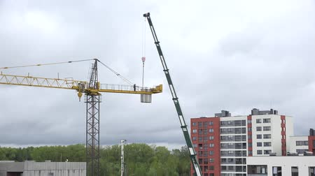 şantiye : VILNIUS, LITHUANIA - MAY 04, 2015: Workers disassemble industrial crane weights parts high in construction site on May 04, 2015 in Vilnius, Lithuania. Zoom in shot. 4K UHD video clip. Stok Video
