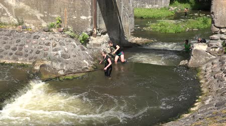 participante : BELMONTAS, LITHUANIA - JUNE 20, 2015: young hurdle race competitor climb hardly through rocky stony fast flowing river on June 20, 2015 in Belmontas, Lithuania. 4K UHD video clip.