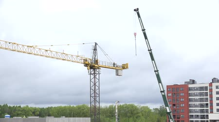 şantiye : VILNIUS, LITHUANIA - MAY 04, 2015: Workers with crane disassemble high industrial crane in construction site on May 04, 2015 in Vilnius, Lithuania. Static tripod shot. 4K UHD video clip.