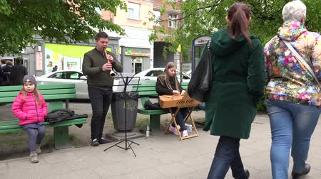plucked : VILNIUS, LITHUANIA - MAY 16, 2015: father play with pipe, girl with zither Lithuanian plucked string  instrument, son with accordion on May 16, 2015 in Vilnius, Lithuania. 4K clip. Panorama view.