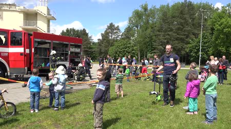 spent : VILNIUS, LITHUANIA - MAY 31, 2015: children with parents enjoy firefighter men performance in public park on May 31, 2015 in Vilnius, Lithuania. National children day. Panorama shot. 4K Stock Footage