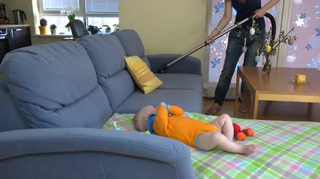 vakum : mother clean dust from couch with vacuum hoover and little baby daughter play near. 4K UHD