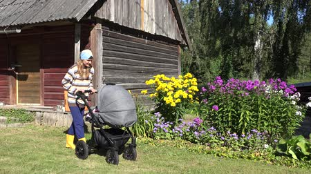 záhon : Happy villager peasant mother try to send baby to sleep in stroller buggy near rural wooden house and flower beds. Static shot. 4K Dostupné videozáznamy