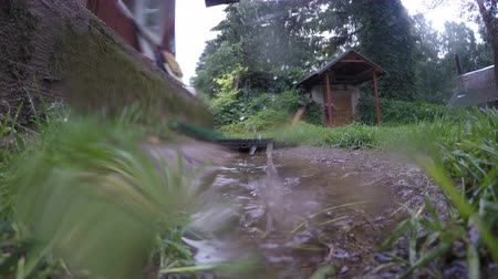 sulky : Rain drops fall and splash in water pool near rural wooden buildings. Wide angle static shot. 4K Stock Footage
