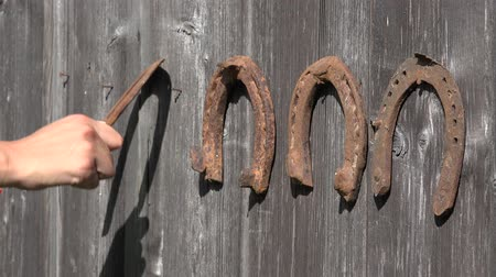 lucky charm : Retro rusty horse shoe hand unhanging on old wooden rural house wall. Static closeup shot. 4K Stock Footage
