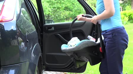 ülés : mother woman open car door and put baby safety chair with infant child on back car seat and fasten with safety belt. Static shot. 4K