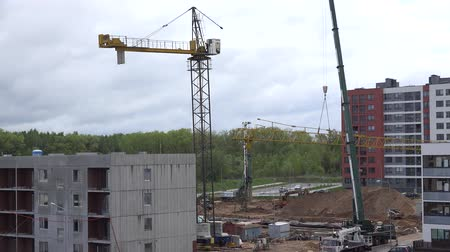 şantiye : VILNIUS, LITHUANIA - MAY 04, 2015: Crane disassemble in construction site on May 04, 2015 in Vilnius, Lithuania. Building multilevel flat houses. Zoom out shot.