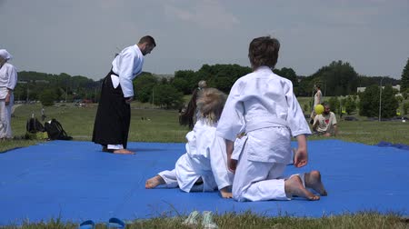 tanítvány : VILNIUS, LITHUANIA - JUNE 07, 2015: Young kids train self protection exercises under master supervision in front of people audience on June 07, 2015 in Vilnius, Lithuania. Static shot.