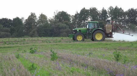 carcinogenic : PANEVEZYS, LITHUANIA - OCTOBER 03, 2015: tractor spray field grass weeds with herbicides near forest before winter season on October 03, 2015 in Panevezys, Lithuania. Panorama shot.
