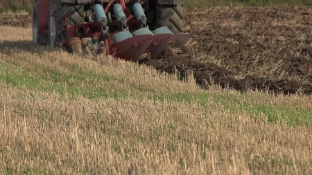 reclaim : agricultural machine tractor plough turn up field soil in autumn season. Static closeup shot. 4K