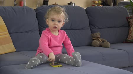 sulky : hysterical baby girl cry using smart phone on sofa. Child show negative emotions. Static closeup shot.