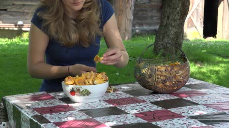 finomságok : Villager girl clean yellow chanterelle mushrooms on table near rural wooden house. Zoom in shot. 4K Stock mozgókép