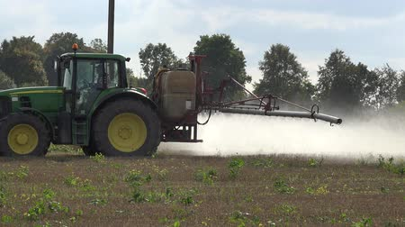 carcinogenic : PANEVEZYS, LITHUANIA - OCTOBER 03, 2015: Farmer drive tractor spray field weeds with herbicide before winter season on October 03, 2015 in Panevezys, Lithuania. Panorama follow shot. 4K Stock Footage