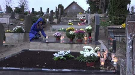 loved : SIRVINTOS, LITHUANIA - NOVEMBER 01, 2015: Woman girl light candle on father grave in cemetery on November 01, 2015 in Sirvintos, Lithuania. People visit graves of relatives in day of Dead. 4K Stock Footage
