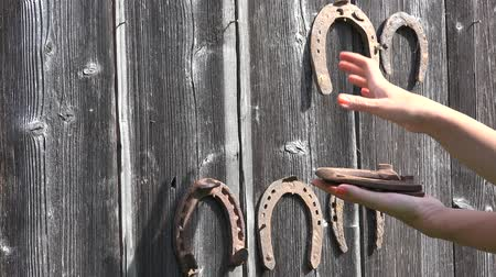 şanslı : Hand take off retro rusty horseshoes hanging on old wooden rural house wall. Closeup. 4K Stok Video
