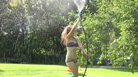 mangueira : woman in swimsuit watering with water hose in the garden. 4K Stock Footage