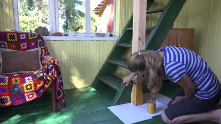 decorador : woman paint wooden column with yellow colour in country home. 4K