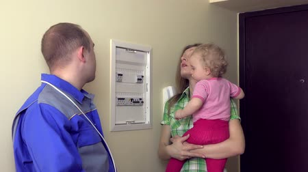 elektryk : Electrician explain for housewife woman with child how to use circuit breaker