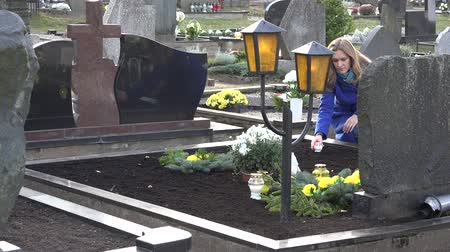 loved : Sad woman put candle on grave of loved father brother in cemetery. 4K