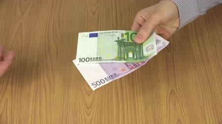 venality : Woman hand pay euro cash 100 and 500 banknotes for man. 4K
