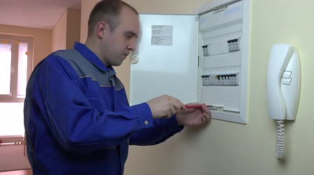unscrewing : Man in blue uniform working on a circuit breaker at flat house Stock Footage