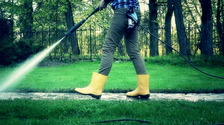 cleaning equipment : female washing stone path in house yard between lawn. Grading effect. Stock Footage