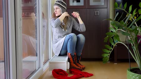čepice : Hot woman undress cap and scarf sitting on radiator. Temperature rising.