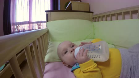 infant formula : baby holding and drinking milk from bottle himself. 4K Stock Footage