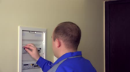 disjuntor : Man in blue uniform turn on circuit breakers on panel box at flat house Stock Footage