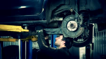freio : Mechanic renew brake system of a vehicle on a car lift. Zoom out.