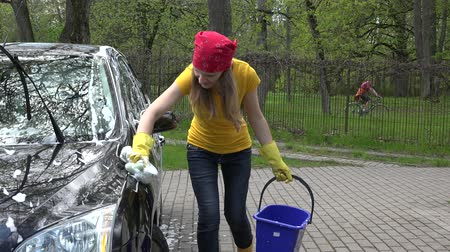 mycie rąk : Pretty woman washes her car with sponge in open air.
