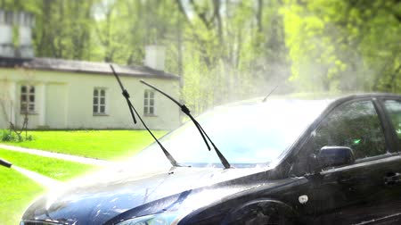 ar : worker washing automobile with high pressure water jet in house yard. Stock Footage